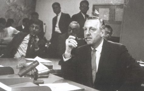 Walter Cronkite sits and smokes a pipe at the CBS news desk with Don Hewitt in the background.