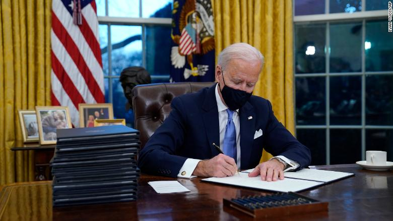 President Joe Biden signs his first executive order in the Oval Office of the White House on Wednesday, Jan. 20, 2021, in Washington.??(AP Photo/Evan Vucci)